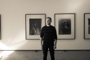The artist Jon Rotman in front of his images of Renata Kawepo (left) and Tareha Te Moanannui.